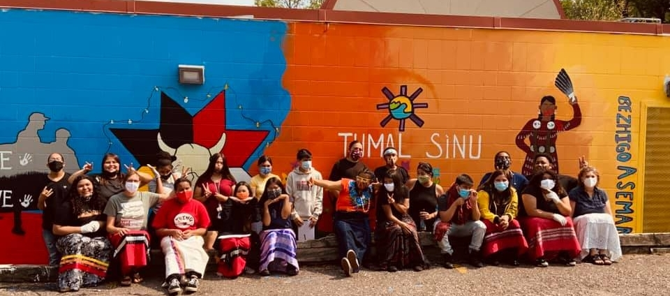youth sitting in front of mural they painted.